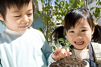Boy and Girl Holding Potted Plant