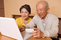 Senior couple using laptop, smiling