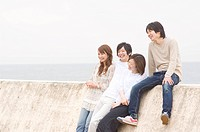 Group of young people leaning on breakwater