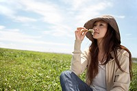 Young Woman Sitting on Field, Smelling Flower