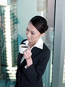 Businesswoman holding a cup of coffee standing by window