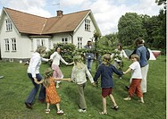 Dans kring midsommarstång Sweden, People dancing around the maypole in garden