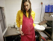 Ung, uttråkad kvinna arbetar som diskare Young Woman Holding Plates, Looking Down