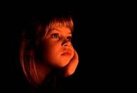 Flicka, 7 år, sitter och funderar i skenet från stearinljus, Girl 4_5, looking away