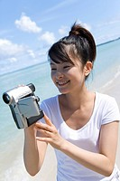 Young woman holding video camera on beach, smiling, Saipan, USA