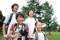 Happy family standing in field, boy holding binoculars