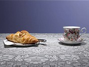 Tea cup and croissant on table (thumbnail)