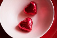 Two heart shaped candies in bowl close-up, directly above (thumbnail)