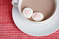 Heart shaped candies in cappuccino close_up, directly above