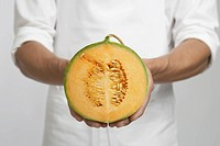 Chef holding half of cantaloupe melon mid section (thumbnail)