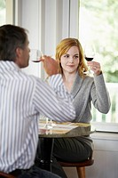 Woman and man tasting red wine focus on background