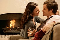 Mid adult couple drinking wine and hugging by fireplace