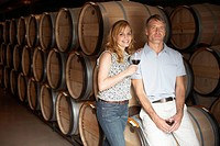 Couple drinking red wine in wine cellar portrait