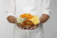 Selection of dried fruits on chef's hands mid section