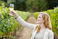 Young woman holding glass of white wine in vineyard