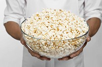 Chef holding bowl of popcorn (mid section)