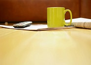Mug, newspaper and remote control on wooden floor close_up