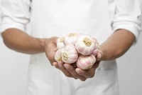 Chef holding garlic onion mid section