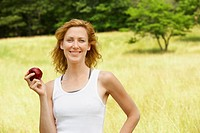 Woman eating apple in field