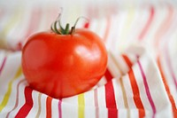 Single tomato on stripy tablecloth (thumbnail)