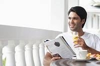Young man having breakfast and reading magazine