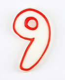 Sugar cookie in the shape of a number nine outlined in red icing