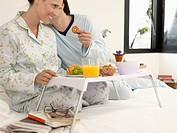 Couple having breakfast on bed, husband whispering to wife