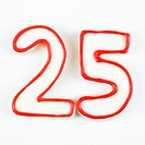 Sugar cookies in the shape of the number twenty five outlined in red icing