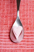 Pink heart shaped candies on table spoon
