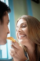 Woman feeding man with cookie