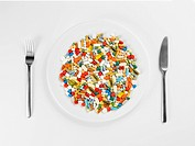 Mixed pills on white plate close_up, directly above