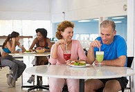 Mature couple eating in health club cafÚ