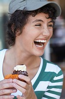 Teenage girl laughing and eating cake