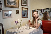 Woman waiting at table in restaurant