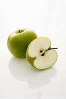 Still life of whole and sliced green apples on white background