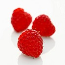 Three red raspberries on white background
