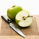 Still life of green apples and knife on cutting board