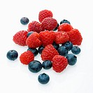 Mixed blueberries and raspberries on white background