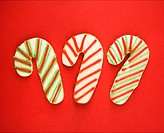 Three candy cane sugar cookies with decorative icing