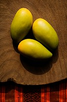 Still life of three wooden mangoes on plate