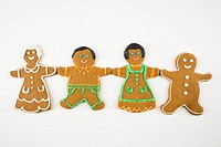 Four male and female gingerbread cookies holding hands