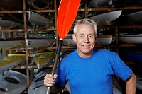 Mature man holding oar by kayaks