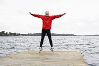 Senior man jumping on jetty (thumbnail)