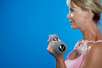 Mature woman exercising with dumbbells