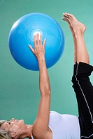 Mature woman exercising abdominals with Swiss ball