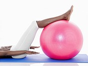 Woman exercising on fitness ball low section