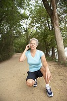 Female jogger talking on cell phone on track