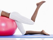 Woman doing leg exercises on fitness ball low section