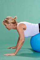 Mature woman exercising on Swiss ball