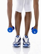 Woman lifting dumbbells low section